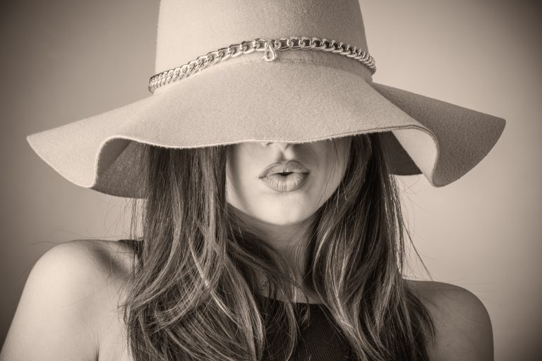 A model's professional head shot where she is wearing a sunhat covering her eyes