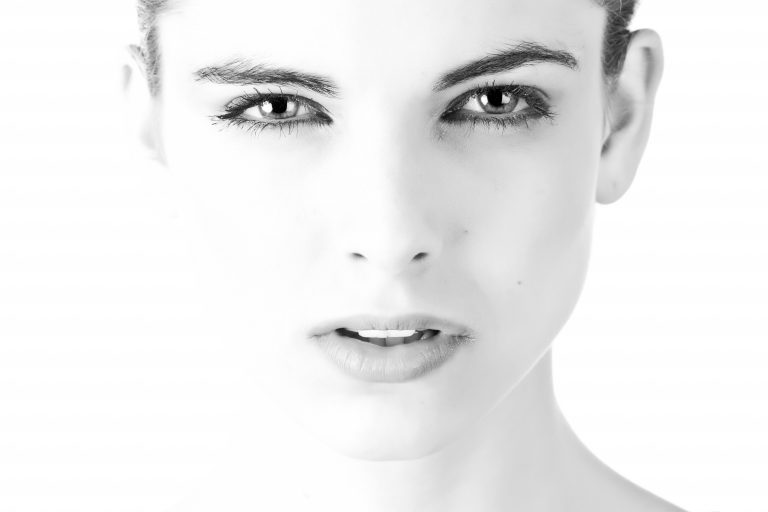 A model's professional head shot in black and white in front of a white background